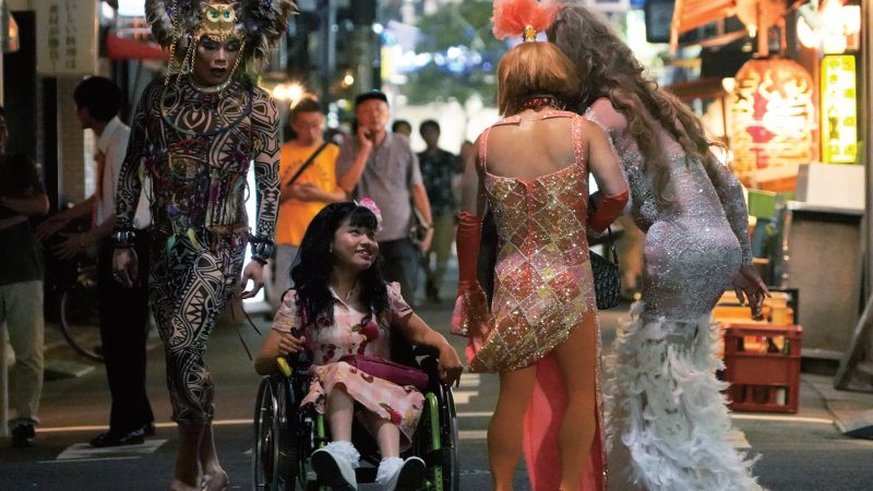 Yuma, a wheelchair user with a pink dress and a flower in her long hair, smiles at 2 people in sequinned dresses.