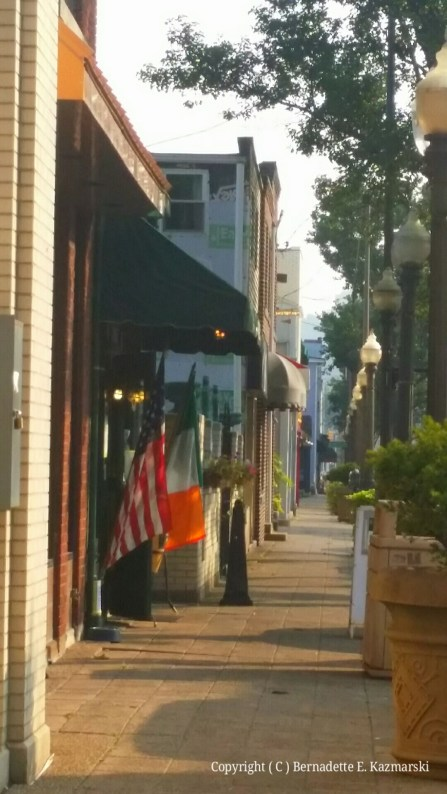 East Main Street, early, Riley's Pour House is open with their flags out.