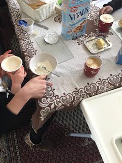 Beim Frühstück mischt das Kind den Quark in den Jogurt