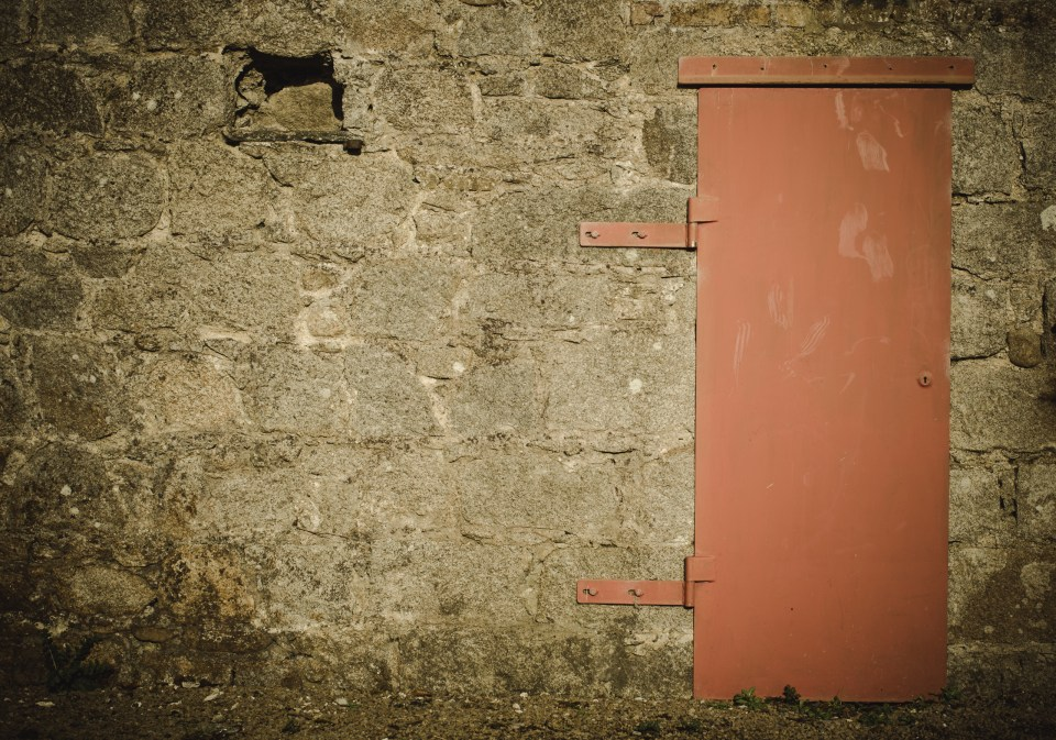 An old stone building with orange door, illustrating Coal Shed Ghosts, a piece of flash fiction.