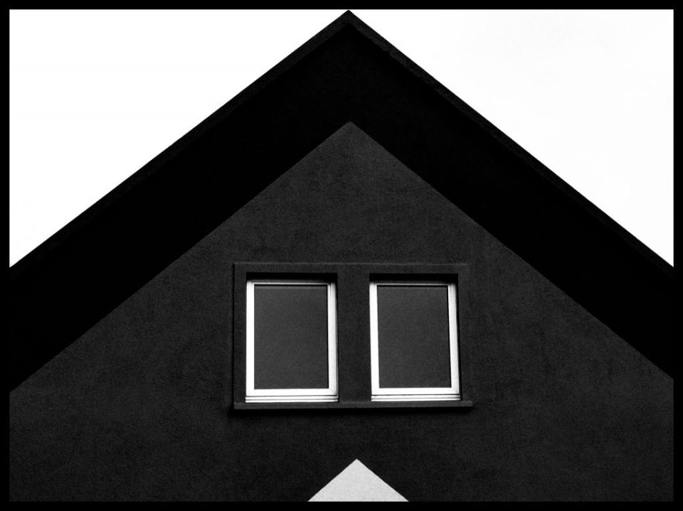 In perfect symmetry, a black and white portrait of a house rooftop. by Bernie Delaney Photography.