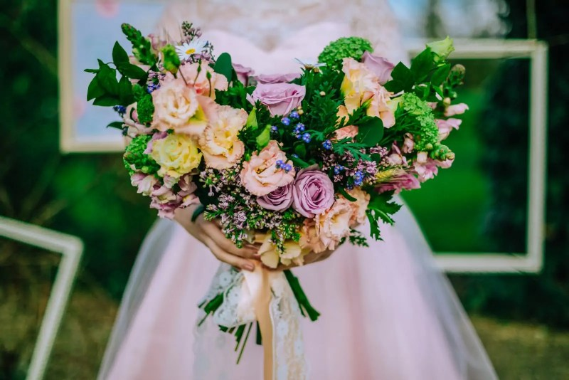 A bride in a pink wedding dress holding a heart-shaped bouquet