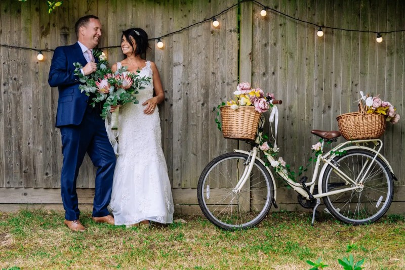 wedding couple with some fairy lights and a bike next to them