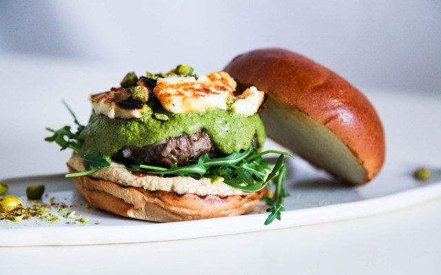 This super tasty lamb burger with halloumi and green herb sauce are a perfect solution for a super gourmet lunch or dinner. The meat is flavoured with Oriental spices, pomegranate molasses and dried barberries and is served on a bed of hummus and peppery rocket and topped with halloumi, a delicious mint, coriander and parsley green herb sauce and crushed pistachios. What's not to love?