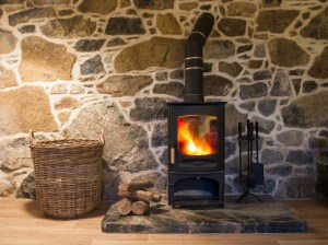 A wood burning stove and logs burning brightly in an old stone cottage.