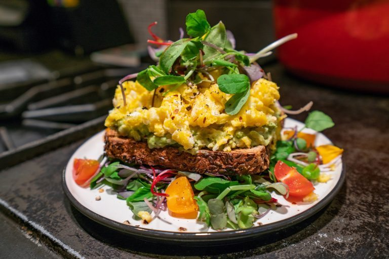 Avocado Toast on sprouted bread with egg and greens