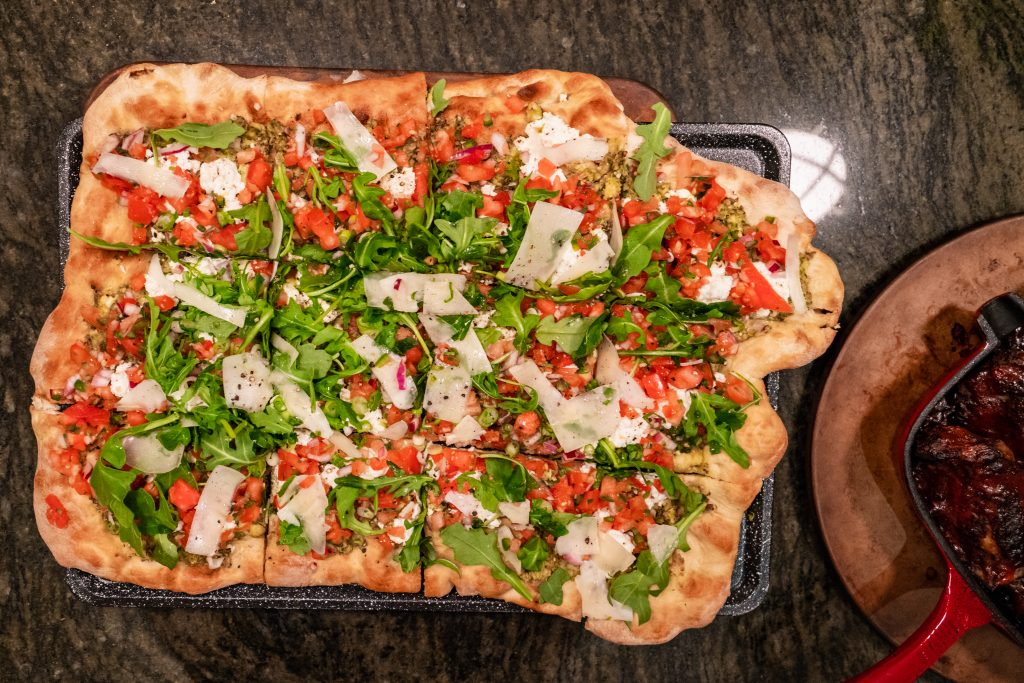 Spring Flatbread with almond pesto, bruschetta, arugula, and cheese