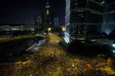 Thousands of protesters attend a rally outside the government headquarters in Hong Kong as riot police stand guard