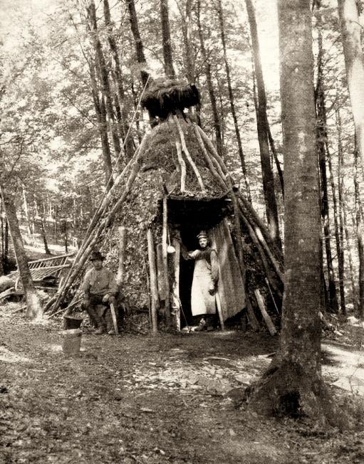 sw-Foto: Köhlerhütte mit Paar im Wald