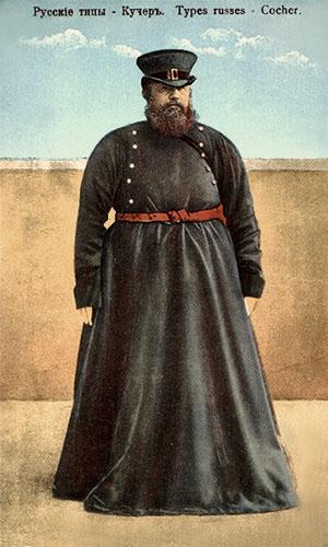 koloriertes Foto: stämmiger, bärtiger, russischer Kutscher in bodenlangem, schwarzblauem Mantel und zylinderartigem Hut, roter Gürtel um den Bauch