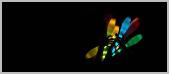 Farbfoto: Dunkelheit: Artist hält leuchtende Jonglierkeulen in der Hand