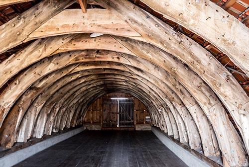 Foto: Blick in das Dachgeschoss eines Bohlenbinderhaus (gebogene Dachbalken)