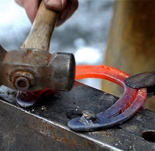 Detail-Farbfoto: glühendes Hufeisen wird auf dem Amboss mit Schmiedehammer bearbeitet