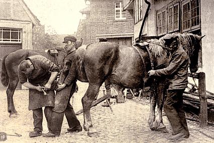 sw-Foto: Hufschmied und Gehilfe beschlagen auf der Kopfstein gepflasterten Dorfstrasse ein Pferd während Bauer dieses am Zaumzeug festhält