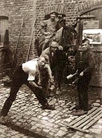sw-Foto: Kopfsteinpflasterhof, zwei Männer und ein Junge beschlagen einem Pferd einen Huf