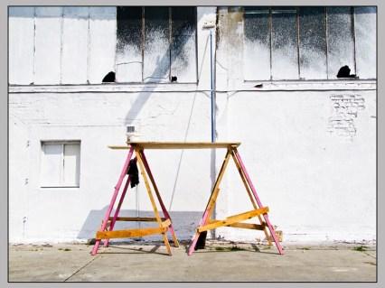 Foto: zwei Arbeitsböcke mit Platte sind aufgebaut, Malerrolle angelehnt an die Wand; ein Teil ist schon weiß gestrichen