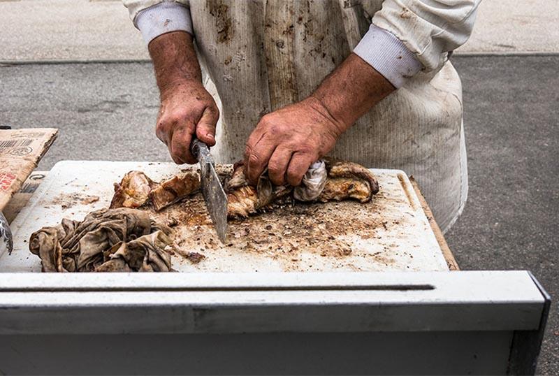 Foto: Metzgerhände zerteilen Lammfleisch mit Hackebeilchen