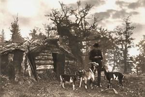 Ziegenhirte im Bayerischen Wald vor einer kleinen archaischen Blockholzhütte mit drei gefleckten Ziegen