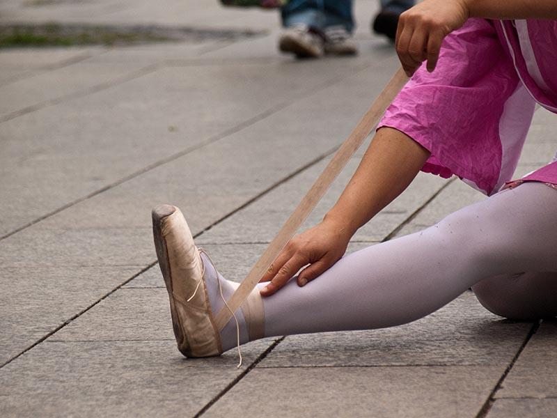 Farbfoto: Frau wickelt ihren Ballettschuh