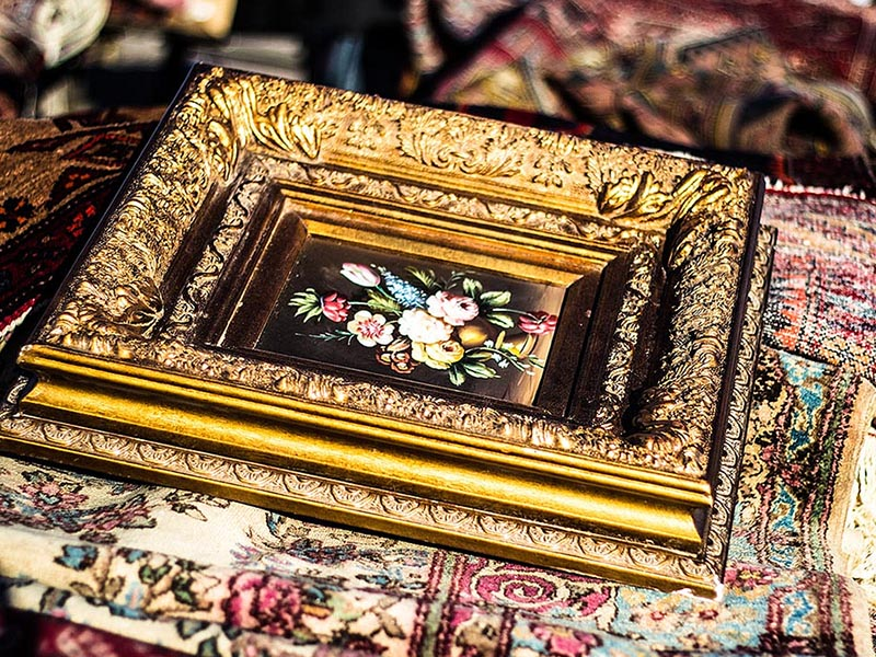 Farbfoto: stark vergoldeter Bilderrahmen mit Blumengemälde