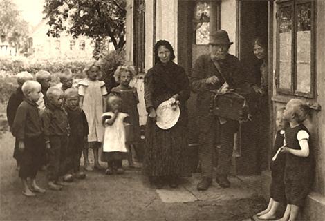 altes sw-Foto: Leierkastenmann umringt von einer barfüßigen Kinderschar