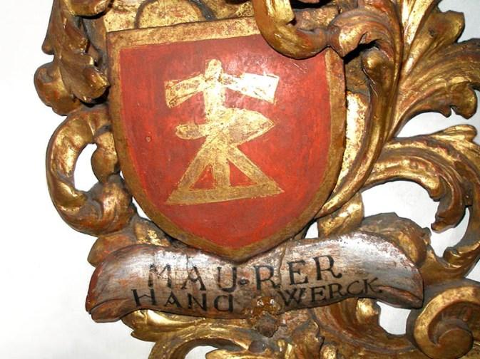 Farbfoto: Schmuckelement, vergoldetes Relief mit rotem Wappen und Aufschrift