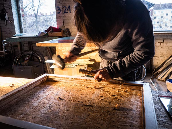 Foto: Frau arbeitet mit Hammer und Stechbeitel am Fensterflügel