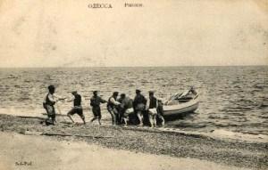 altes sw-Foto: Männer ziehen Boot aus dem Meer an den Strand