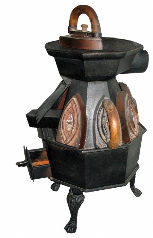 alter kleiner Ofen, auf dem ein altes Bügeleisen steht