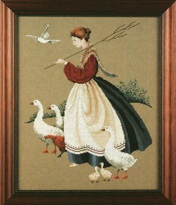 Farbfoto: Gerahmtes Kreuzstichbild zeigd Gänsemagd mit Gänsen
