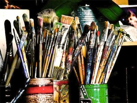 Farbfoto: viele benutzte Pinsel voller Farbe in zwei Dosen