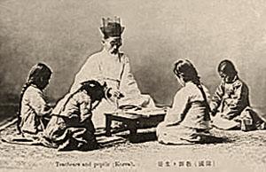 sw-Foto: vier Schülerinnen sitzen mit ihrem Lehrer um ein flaches Tischchen auf dem Teppich und haben Bücher aufgeschlagen