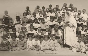 s/w Foto: stehender Lehrer mit Turban und zum Gruppenbild aufgereihte Schüler, die meisten mit einem aufgeschlagenen Buch