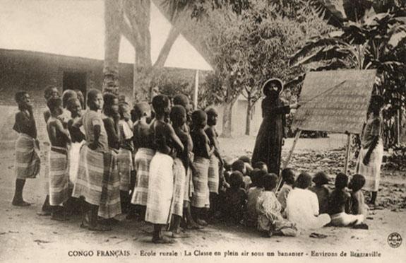 s/w Foto: im Freien unter Banananstaude Lehrer an einer Stehtafel, links davor sitzende und stehende Schüler