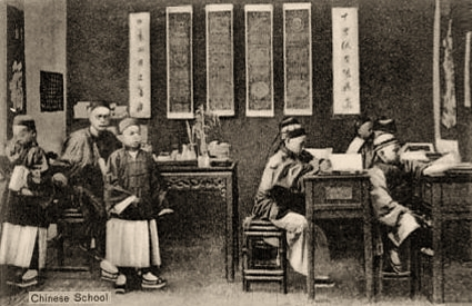 s/w Foto: chinesischer Lehrer an einem Sitzpult mit mehreren Schülern in einem Klassenzimmer