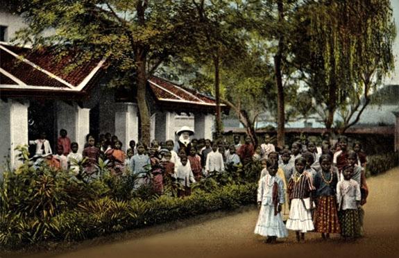 Farbfoto: vor der Schule zum Gruppenbild aufgestellte Lehrerin mit Schülerinnen