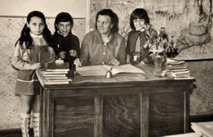 s/w Foto: Lehrerin an einem Sitzpult mit drei Schülerinnen in einem Klassenzimmer