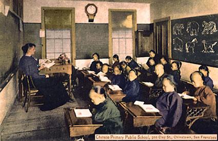 s/w Foto: weiße Lehrerin an einem Sitzpult vor an Einzelschreibpulten sitzenden chinesischen Schülern in einem Klassenzimmer