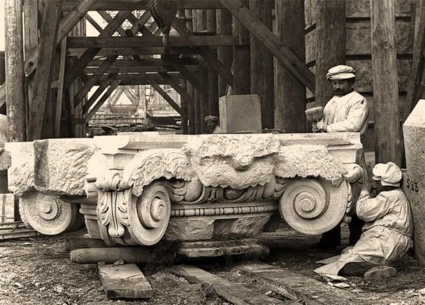 s/w Foto: zwei Steinmetze bei der Bearbeitung eines Säulenkapitells