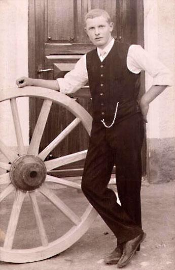 Foto: junger Handwerker steht neben einem Holzrad und stützt sich darauf auf