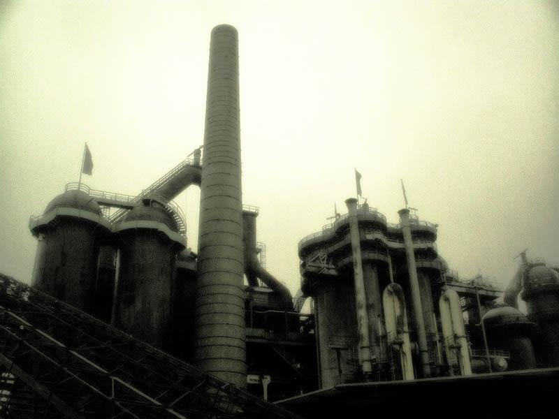 monochromes Foto: Eisenhütte mit Schornstein und Silos: unheimlich wirkend