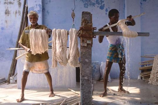 Farbfoto: zwei Männer beim Auswringen von Baumwolle nach dem Waschen, mittels Stöcken wird der Stoff zusammen gedreht