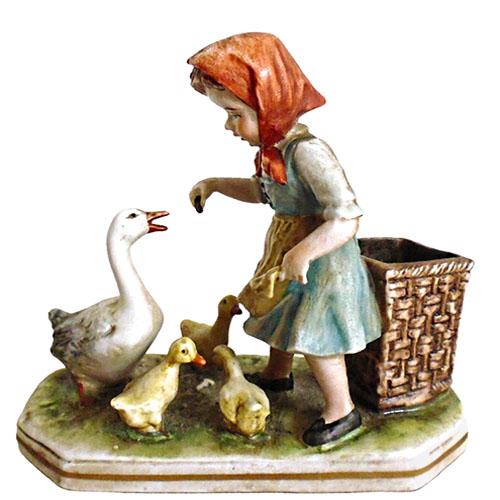 Porzellanfigur: kleines Gänseliesel mit rotem Kopftuch füttert Gänsemama und drei Küken, dahinter steht großer viereckiger Tragekorb