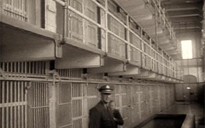 altes sw-Foto: Gefängniswärter im Gang vor Gitter-Zellentüren