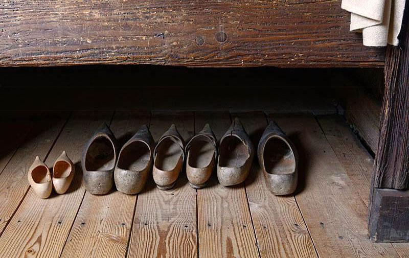Farbfoto: vier Paar historische Holzschuhe, eins davon in Kindergröße