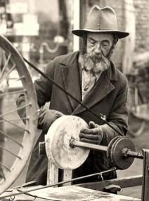 s/w Foto: alter Scherenschleifer mit Hut und Bart am Straßenrand bei der Arbeit am Schleifstein