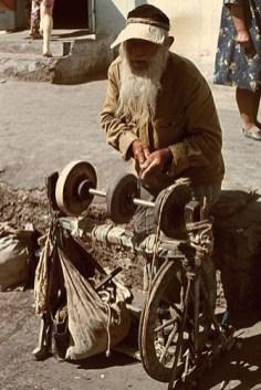 Farbfoto: alter langbärtiger Mann mit großer Schirmmütze an seiner Schleifvorrichtung stehend bei der Arbeit