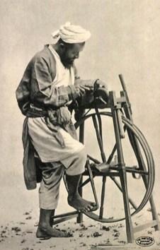 Scherenschleifer, Messerschleifer alte s/w Fotopostkarte: Inder mit Turban bedient im Sand stehendes Schleifgerät mit einer Fußkurbel, während er ein Messer schärft