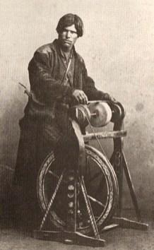 altes s/w Foto: an bockartigem, bäuerlich bemaltem Schleifgerät stehend arbeitender, junger russischer Messerschleifer