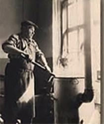 altes s/w Foto: Schwarzfärber rührt mit Färbestab im Färbebottich herum, der eine Art Ofen mit Ofenrohr eingelassen ist